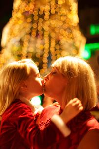 イルミネーションの前でキスをする女の子とママの写真素材 [FYI02019263]