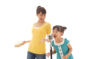 歌う女の子とタンバリンをたたくお母さんの写真素材 [FYI02019285]