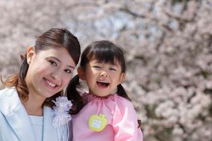 桜の前でお母さんと寄り添う幼稚園児の女の子の写真素材 [FYI02019548]