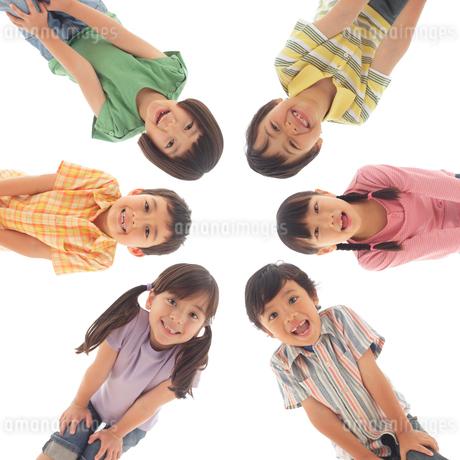 円になって覗き込む6人の小学生の子ども達の写真素材 [FYI02019554]
