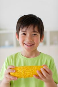 とうもろこしを食べるハーフの男の子の写真素材 [FYI02019624]