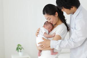 新生児を抱っこする新米ママとパパの写真素材 [FYI02019673]