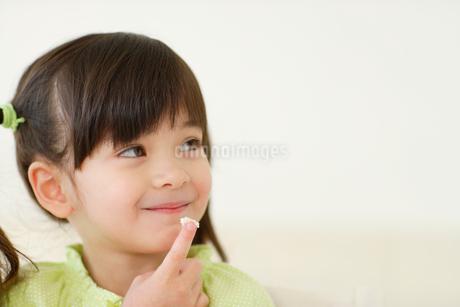 クリームをなめる女の子の写真素材 [FYI02019693]