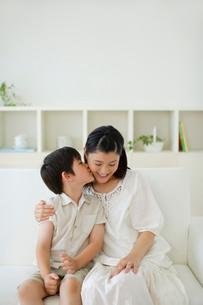 ソファーに座りお母さんにキスする男の子の写真素材 [FYI02019758]