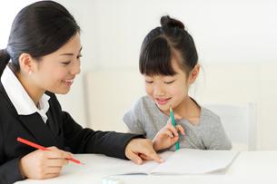 先生に勉強を教わる女の子の写真素材 [FYI02019817]