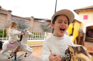 メリーゴーランドに乗る外国人の男の子と女の子の写真素材 [FYI02019818]