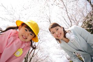 カメラを覗き込むスーツ姿のお母さんと幼稚園児の女の子の写真素材 [FYI02019820]