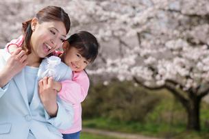 桜の前でお母さんを抱きしめる幼稚園児の女の子の写真素材 [FYI02019890]