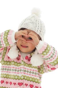 セーターを着て手の隙間から覗く女の子の写真素材 [FYI02020006]