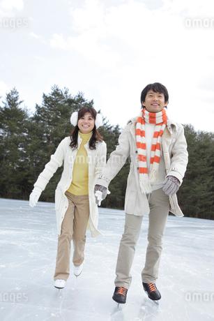 手を繋いでスケートを滑るカップルの写真素材 [FYI02020017]