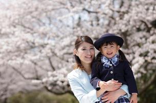 桜の前で制服姿の女の子を抱きしめるスーツ姿のお母さんの写真素材 [FYI02020350]