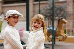 メリーゴーランドの前に立つ外国人の男の子と女の子の写真素材 [FYI02020373]