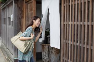 のれんをくぐって店を訪ねる一人旅の女性の写真素材 [FYI02020387]