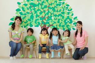 木の壁面の前に座る保育園児と先生の写真素材 [FYI02020421]