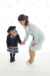 桜の花びらを見上げる制服姿の幼稚園児とお母さんの写真素材 [FYI02020437]