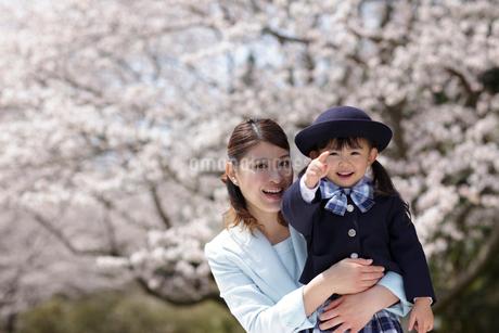 桜の前で制服姿の女の子を抱きしめるスーツ姿のお母さんの写真素材 [FYI02020490]