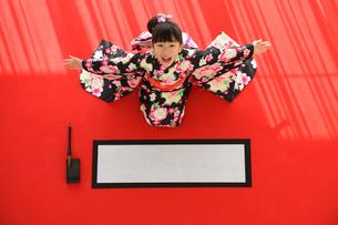 振り袖を着て書初めをする女の子の写真素材 [FYI02020539]