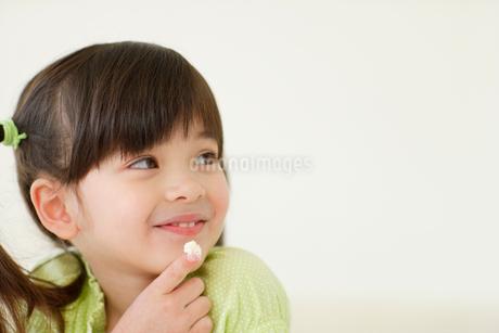クリームをなめる女の子の写真素材 [FYI02020547]
