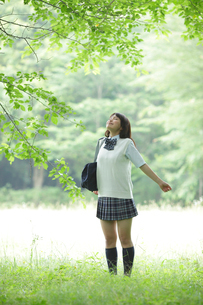 新緑の中で深呼吸をする女子高生の写真素材 [FYI02020602]