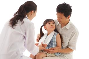 診察を受ける女の子とお父さんの写真素材 [FYI02020654]