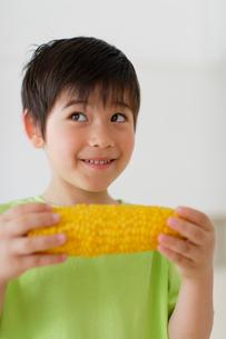 とうもろこしを食べるハーフの男の子の写真素材 [FYI02020671]
