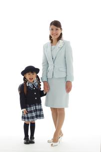 手を繋ぐ制服姿の幼稚園児とスーツ姿のお母さんの写真素材 [FYI02020699]