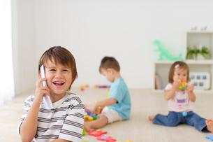 子供部屋で遊ぶハーフの兄弟と携帯電話をかけるハーフの男の子の写真素材 [FYI02020756]