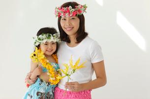 フラダンスの衣装を着てお花を持っている親子の写真素材 [FYI02020768]