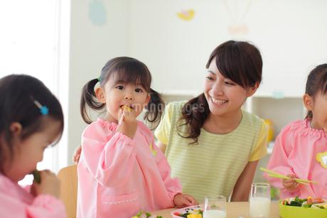 お弁当を食べる幼稚園児と先生の写真素材 [FYI02020828]