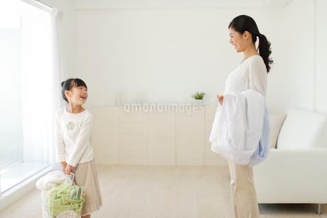 洗濯物を運ぶお母さんと女の子の写真素材 [FYI02020892]