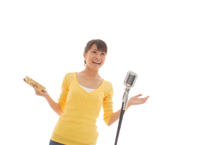 タンバリンを叩きながら歌う女性の写真素材 [FYI02021044]