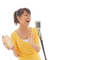 タンバリンを叩きながら歌う女性の写真素材 [FYI02021133]