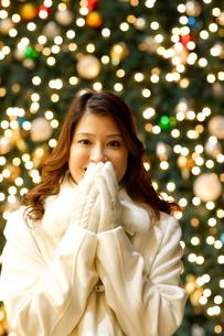 クリスマスツリーの前に立つ女性の写真素材 [FYI02021231]