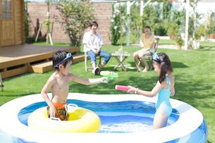 プールで水鉄砲をする子供と両親の写真素材 [FYI02021377]