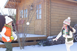 雪合戦をして遊ぶ男の子と女の子の写真素材 [FYI02021392]
