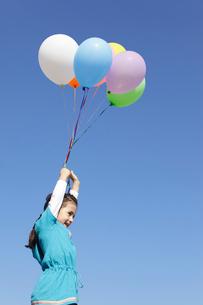 青空の下カラフルな風船を持つ女の子の写真素材 [FYI02021395]