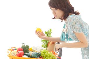 ショッピングカートで買い物をする若い女性の写真素材 [FYI02021501]
