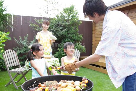 庭でバーベキューをする家族の写真素材 [FYI02021633]