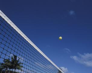 テニスネットの上を飛ぶボールの写真素材 [FYI02021790]