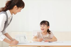 先生に勉強を教わる女の子の写真素材 [FYI02021915]