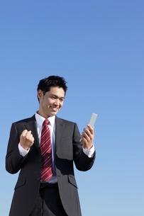 携帯を持ちガッツポーズをするスーツ姿の男性の写真素材 [FYI02021950]