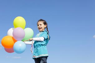 青空の下カラフルな風船を持つ女の子の写真素材 [FYI02021958]