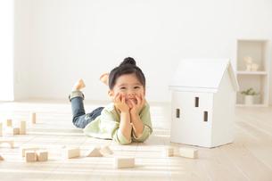 リビングで寛ぐ女の子と木の家の写真素材 [FYI02021998]