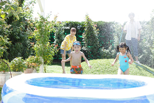 庭でシャワーの水遊びをする親子の写真素材 [FYI02022013]