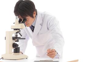 顕微鏡を覗く白衣の若い男性の写真素材 [FYI02022083]