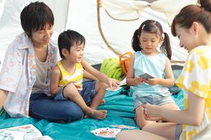 テントの中でトランプをする家族の写真素材 [FYI02022192]