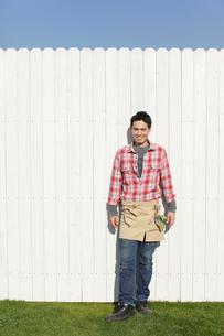 白壁の前に立つ庭師の男性の写真素材 [FYI02022237]