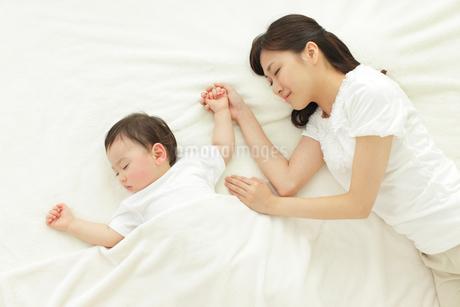 昼寝をする赤ちゃんと添い寝をする母の写真素材 [FYI02022344]