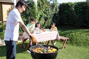 庭でバーベキューを楽しむ家族の写真素材 [FYI02022565]