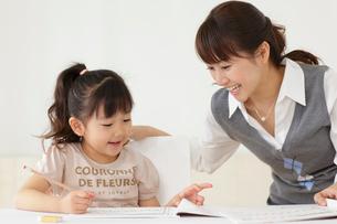 先生に勉強を教わる女の子の写真素材 [FYI02022600]